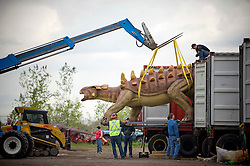 "Apr 25, 2012: A model Ankylosaurus dinosaur is unloaded from a trailer and will be set in place at Field Station: Dinosaurs in Secaucus, NJ over the next 12 days. The dinosaur theme park is set to open in late May and will be one of the only permanent dinosaur exhibits in the country to use advanced robotics to make the beasts ""move"" in response to visitors. Credit: Rob Bennett for The Wall Street Journal Slug:"