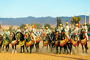 "Horse riders from across Morocco perform at the 2016 Kelaat M'Gouna rose festival fantasia event, Kelaat M'Gouna, Dades and Tinghir Province of Southern Morocco, 2016-05-13.<br /> <br /> Fantasia is a horse riding performance based tradition which displays the skilled horsemanship of riders from different regions of Morocco at cultural festivals (known as a 'Moussem' in Moroccan Darija) and important weddings. <br /> <br /> A fantasia is referred to by locals as being ""Lab el Baroud"" (""the gunpowder play"") and involves the horse riders charging in a perfect line and firing one round using a musket rifle into air at exactly the same time so only one single shot is heard by the audience."