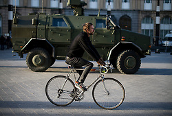 "© Licensed to London News Pictures. 23/11/2015. Brussels, Belgium. A man rides his bike past a military vehicle parked next to Brussels Central Station where the city is currently on ""lockdown"" amid ""imminent threat"" of Paris-style bomb and gun attacks. Photo credit: Ben Cawthra/LNP"
