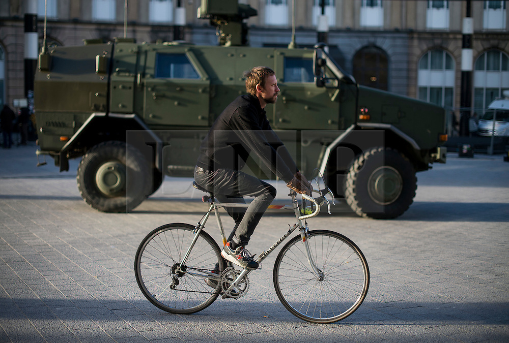 """© Licensed to London News Pictures. 23/11/2015. Brussels, Belgium. A man rides his bike past a military vehicle parked next to Brussels Central Station where the city is currently on """"lockdown"""" amid """"imminent threat"""" of Paris-style bomb and gun attacks. Photo credit: Ben Cawthra/LNP"""