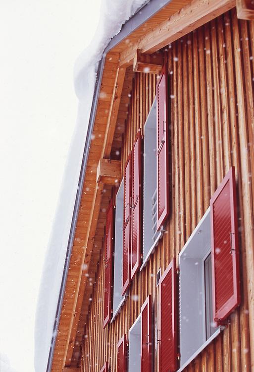 Facade of new chalet with snow falling Malbun, Leichstenstein
