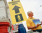Man sells airshow programmes under council sign for evacuation routes postedd during local airshow weekend.