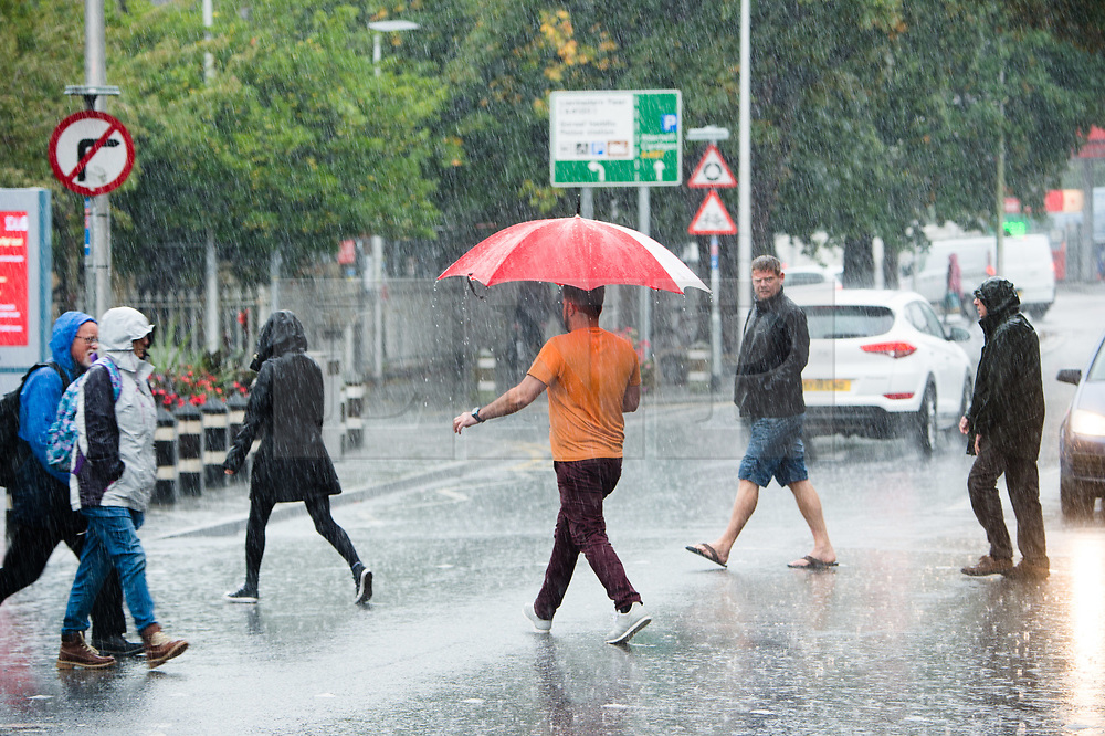 © Licenced to London News Pictures. Aberystwyth Wales UK, Thursday 20 September 2018. UK Weather: Downpours of torrential autumn rain drenches shoppers as they walk along the street in Aberystwyth Wales. Photo © Keith Morris / LNP