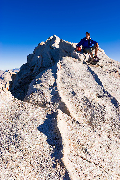 Climber on the summit of Bear Creek Spire, John Muir Wilderness, Sierra Nevada Mountains, California