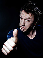 studio portrait on black background of a funny expressive caucasian man thumb up satisfied
