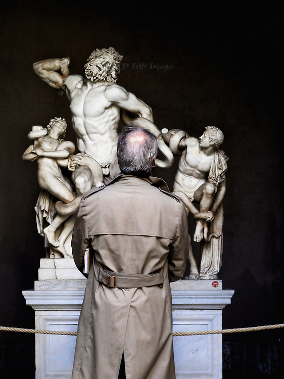 Laocoon sculpture, Vatican museum, man in a khaki colored raincoat, balding, gray hair, seen from behind studying the statue.  He interacts with it.