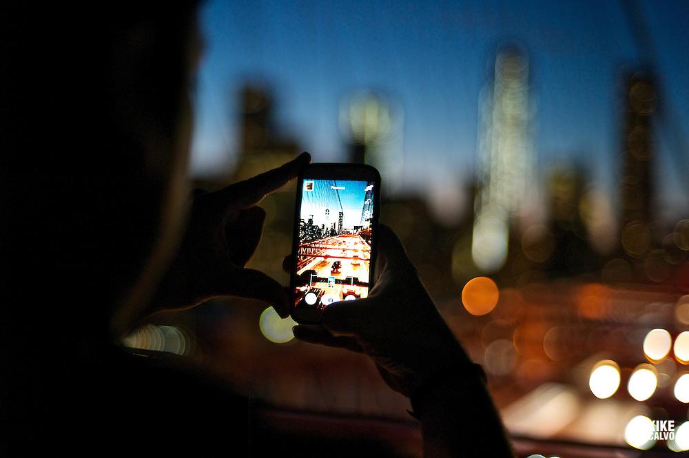 MR man taking photos of downtown Manhattan at night using his cel phone Samsung Galaxy