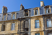 Fire damaged building alongside newly cleaned facades near Place de la Bourse in old Bordeaux