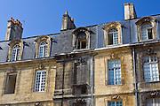 Fire damaged building alongside newly cleaned facades near Place de la Bourse in old Bordeaux