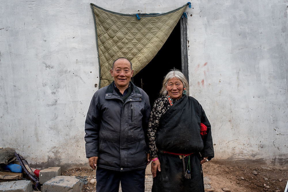 A couple poses for a portrait in front of their home in Zado, Tibet (Qinghai, China).