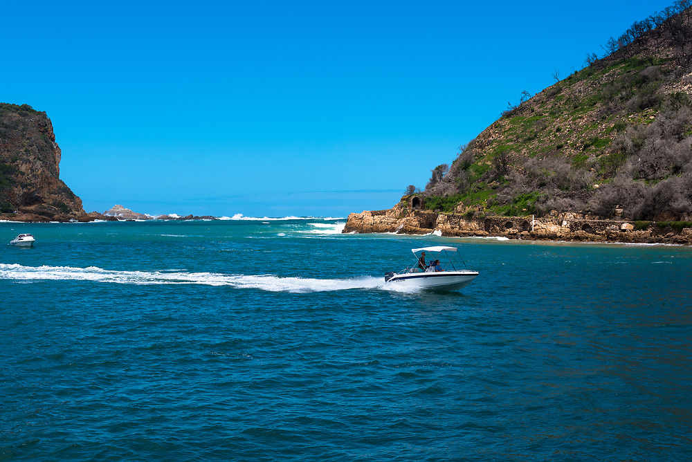 Mossel Bay, South Africa -- January 9, 2018 -- A motorboat cuts a path across Knysna Lagoon leaving a wake behind it. Editorial Use Only.