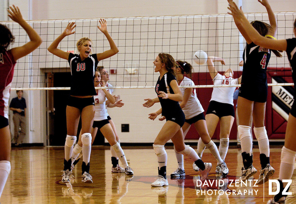 After a powerful spike and before the ball hits the ground, Metamora High School's Angela Rego, (10), celebrates the point with teammates on the way to a comeback win against Morton High School.