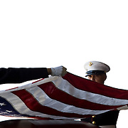 A pair of United States Marines removes the flag from the casket of Cpl. Joshua Meadows as they prepare to present it to his widow, Angela Meadows, during his funeral.