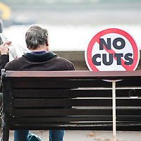 London, UK - 20 October 2012: a man sits near a sign reading 'No Cuts' during the TUC-organised march 'A future that works' against austerity cuts in central London.