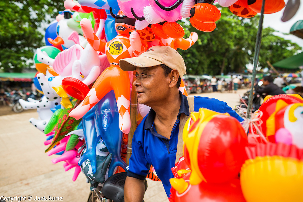 14 JUNE 2013 -  PATHEIN, AYEYARWADY, MYANMAR: An inflatable toy vendor in Pathein, Myanmar. Pathein, sometimes also called Bassein, is a port city and the capital of the Ayeyarwady Region, Burma. It lies on the Pathein River (Bassein), which is a western branch of the Irrawaddy River. It's the fourth largest city in Myanmar (Burma) about 190 km west of Yangon.   PHOTO BY JACK KURTZ