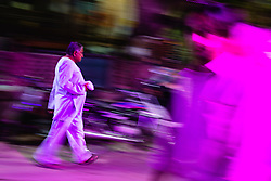 Motion-blur of a man walking at night, street life of Jodphur, Jodphur, Rajasthan, India,