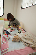 Asawa Pet Pasture elder care for Dogs, Pet of Owners who can not give the  care they feel  their pet deserves.<br /> Saito  Yuki  (grey sweater )   and her co worker Kana Okazaki  are providing the  extra care need to  elderly dogs or dogs with special needs.<br /> for story by Richard Lloyd Parry