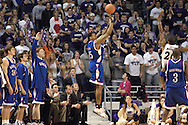 Brandon Rush (C) of Kansas hits a three pointer from the corner over Kansas State's Cartier Martin (20), during the second half at Bramlage Coliseum in Manhattan, Kansas, March 4, 2006.  The Jayhawks won 66-52.