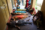 10th August 2011, Jhunjhunu.Women lie recovering from anaesthesia in an open-sided corridor after their sterilisation operation in a 'Sterilisation Camp' set up at, Jhunjhunu Health Centre, Rajasthan, India.<br /> <br /> When Jhunjhunu district began to fall behind in its 2011 sterilisation target of 21,000 per year Senior Medical Officer for Jhunjhunu district Dr Sanataram Sharma, borrowing an idea from the district collector, introduced an incentive scheme to encourage sterilisation uptake. The scheme offers the opportunity for participants (overwhelmingly female) to be entered into a raffle to win a flat screen TV or a motorcycle or a Tata Nano car. With India's burgeoning population aggressive family planning initiatives are being promoted but human rights and other NGO's say the approaches are coercive and target the poor and disadvantaged. It also harks back to Sanjay Ghandi's infamous enforced sterilisation policy enacted during India's state of emergency between 1975 and 1977.<br /> <br /> PHOTOGRAPH BY AND COPYRIGHT OF SIMON DE TREY-WHITE a photographer in Delhi<br /> <br /> + 91 98103 99809<br /> <br /> email: simon@simondetreywhite.com photographer in delhi