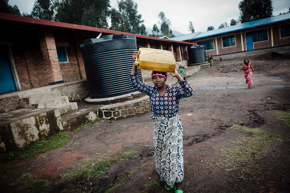Beatrice collects water from the tap at her local school. The school was built with funding from ActionAid. Shingiro District, Rwanda