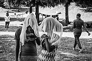 Two female migrants playing with a scarf
