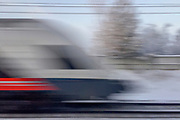 An image of a passing commuter train is blurred by the high speed of the train. Commuter trains are an important part of the infrastructure in many Norwegian cities. This one is from outside Jessheim.