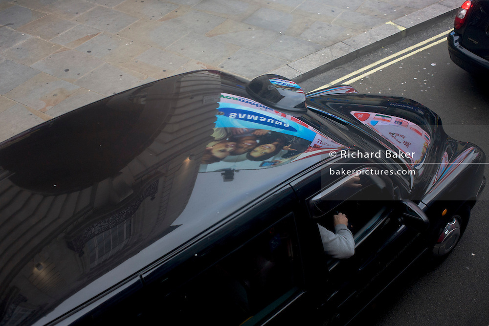 Black London taxi cab and reflections of Piccadilly Circus ads.