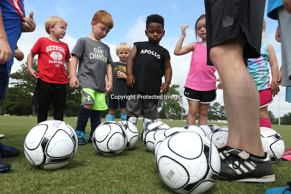 A group of 4 and 5 year olds place their soccer balls at the feet of Christian Dane, director of coaching, as they gather for a small break during the Tupelo Youth Soccer Association's Soccer Camp on Tuesday morning at the soccer fields at Ballard Park. The camp runs this week from 9 AM to noon with the 4 and 5 year olds going to 10:30 and one later this summer in July 10-14.