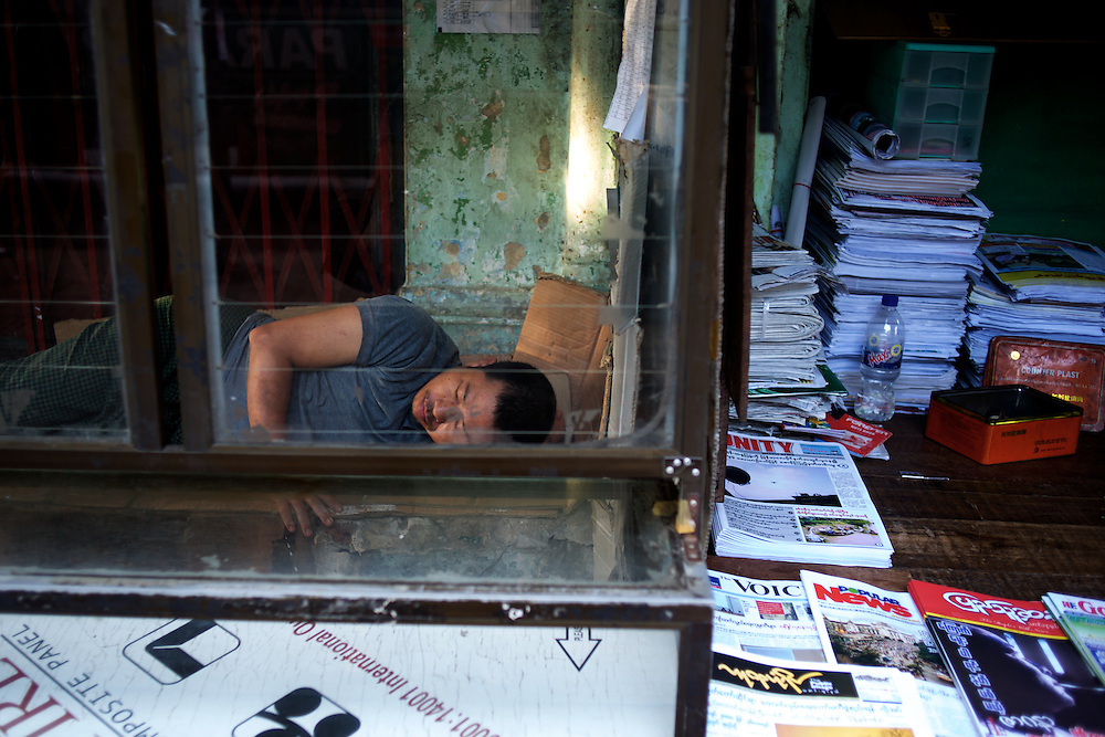 May 09, 2013 - Yangon, Myanmar: A man sleeps in a stall beside a newspaper stand in central Yangon. CREDIT: Paulo Nunes dos Santos