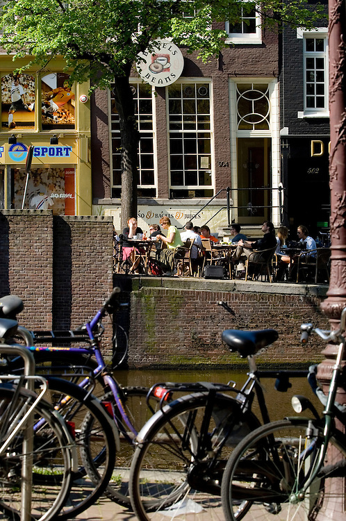 Tourists and locals enjoy a coffee and snack at an Amsterdam canalside cafe in the Spring sunshine.