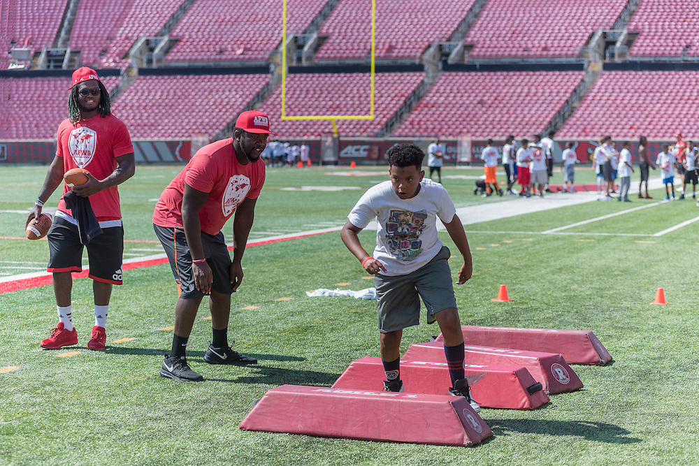 Lorenzo Mauldin, left, and Aaron Epps watch as Jaylan Barnicott, 11, runs a practice drill during the American Football Without Barriers youth football camp at the University of Louisville's Papa John's Cardinal Stadium. June 25, 2016