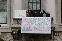 "© Licensed to London News Pictures. 30/12/2015. London, UK. Squatters sits on the balcony of the Royal Mint building with a banner saying ""Take back the city"". Squatters have occupied the former Royal Mint building, located opposite the Tower of London on the border of the City of London to protest against homelessness and highlight how empty buildings could provide shelter for rough sleepers. The site was previously used to manufacture British coins but is currently vacant and activists argue that this along with other vacant commercial buildings could be used to provide short term shelter for the homeless. Photo credit : Vickie Flores/LNP"