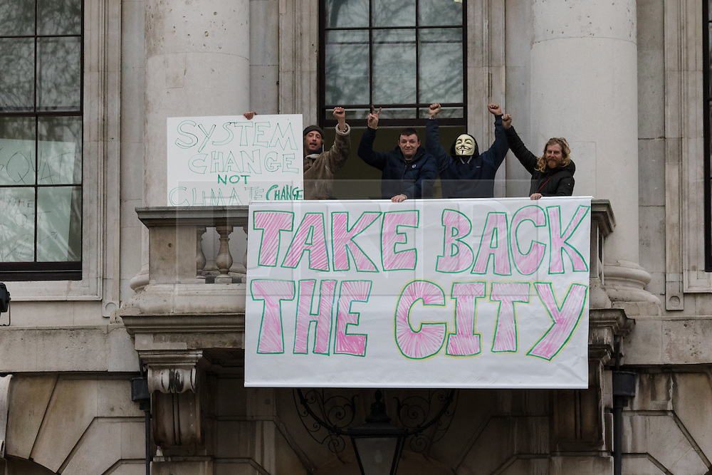 """© Licensed to London News Pictures. 30/12/2015. London, UK. Squatters sits on the balcony of the Royal Mint building with a banner saying """"Take back the city"""". Squatters have occupied the former Royal Mint building, located opposite the Tower of London on the border of the City of London to protest against homelessness and highlight how empty buildings could provide shelter for rough sleepers. The site was previously used to manufacture British coins but is currently vacant and activists argue that this along with other vacant commercial buildings could be used to provide short term shelter for the homeless. Photo credit : Vickie Flores/LNP"""