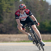 A male triathlete rounds a hairpin turn on his bicycle.