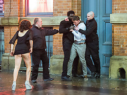 © Licensed to London News Pictures . 01/01/2015 . Manchester , UK . Bouncers push a man away from Victoria's Lap Dancing Bar on Dantzic Street as a woman pulls herself from the ground . Revellers usher in the New Year on a night out in Manchester City Centre .  Photo credit : Joel Goodman/LNP