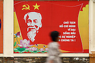 A blurred figured walks past a propaganda billboard praising former president Ho Chi Minh, Ho Chi Minh City, Vietnam, Southeast Asia