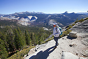 female hiker enjoys the view on the way to Half Dome rock at Yosemite national Park, California USA