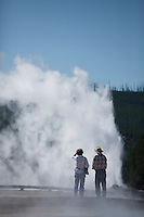 Two people watching Old Faithful Geyser in Yellowstone National Park, WY.