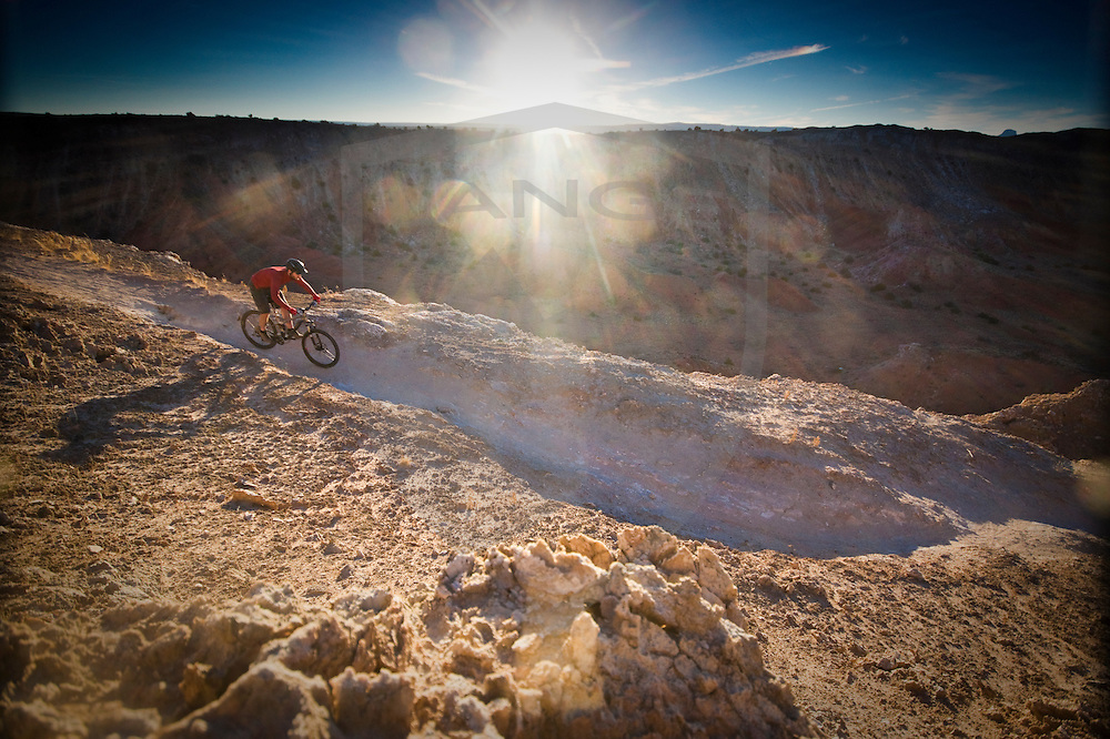 rider christian prout on the vast geology of the center spine route, white mesa bike trails, near san ysidro, new mexico, usa.