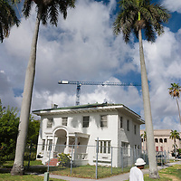 A construction worker walks by the vintage Miami home at 19th street and Biscayne Blvd. before demolition.  Image from a series called Paradise Lost, the changing face of Miami.