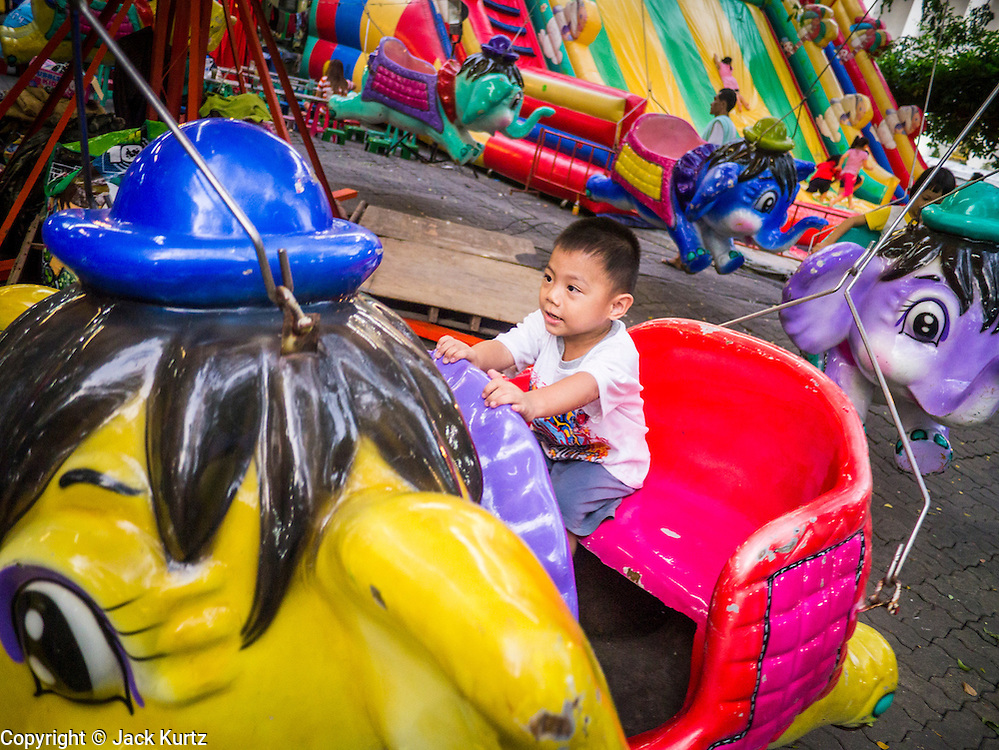 "27 NOVEMBER 2012 - BANGKOK, THAILAND:   A child on a ride on the midway at the Wat Saket Temple Fair in Bangkok. Wat Saket, popularly known as the Golden Mount or ""Phu Khao Thong,"" is one of the most popular and oldest Buddhist temples in Bangkok. It dates to the Ayutthaya period (roughly 1350-1767 AD) and was renovated extensively when the Siamese fled Ayutthaya and established their new capitol in Bangkok. The temple holds an annual fair in November, the week of the full moon. It's one of the most popular temple fairs in Bangkok. The fair draws people from across Bangkok and spills out in the streets around the temple.   PHOTO BY JACK KURTZ"