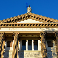Funen's Art Museum in Odense, Denmark <br /> The gorgeous Neo-classical design of Funen's Art Museum has the appearance of a Greek temple. Among its features are dentil molding outlining the pediment, Corinthian columns and a statue of a robed warrior holding a spear. Also notice the delicate bas-reliefs depicting scenes of Danish history. Fyns Kunstmuseum was built in 1885. Inside are works of art from the 17th century through Danish Modernism.