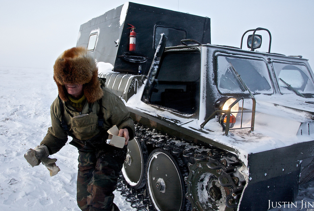 "Andrei exits his snow tank to deliver light bulbs to colleagues in the colony set up by oil and gas prospecting company ""Siesmorevzedka"" in the Arctic tundra. Typically, they work in the cold, isolated Arctic tundra for the entire winter, returning to civilisation only in spring."