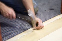 Carpet fitter laying a carpet,