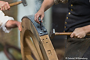 Wheelwrights straking a French artillery wheel.