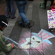 Mercedes Huddleston, 3, walks past chalk art during a combined Occupy Seattle and Act Now to Stop War and End Racism (ANSWER) protest at Westlake Park on Friday, October 7, 2011. Hundreds of people gathered for the two coinciding protests. (Joshua Trujillo, seattlepi.com)