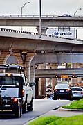 "A superboard sign at a highway interchange in Austin says "" I love Traffic""."