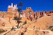Family hiking under rock spires on the Queen's Garden Trail, Bryce Canyon National Park, Utah USA