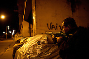 A police officer takes position during an operation to occupy the Caju slum complex during a cojoint operation to install a Pacifying Police Unit (UPP) in Rio de Janeiro, Brazil, Sunday, March 3, 2013. The action is part of a program aiming to drive armed drug gangs out of Rio's slums.