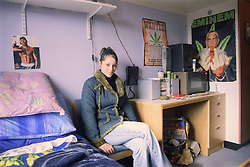 Young woman sitting on chair in bedsit at direct access hostel for homeless and vulnerably housed young people,